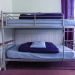 Our bunk beds with our warm comforters and fluffy pillows.